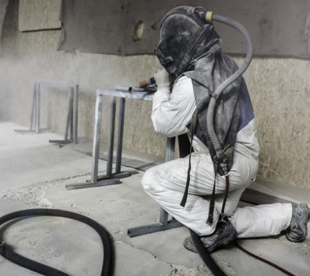 pracownik podczas piaskowania